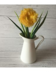bright yellow felt flower in small white jug on whitewash wooden table